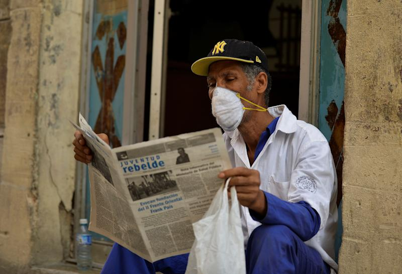 A man reads a newspaper as he wears a face mask in Havana, on March 12, 2020 as the world battles the outbreak of the new coronavirus, COVID-19. - Cuba registered its first three cases on Wednesday. Three Italian tourists, who had arrived Monday in Havana, all tested positive for the virus and have been quarantined. (Photo by Yamil LAGE / AFP) (Photo by YAMIL LAGE/AFP via Getty Images)