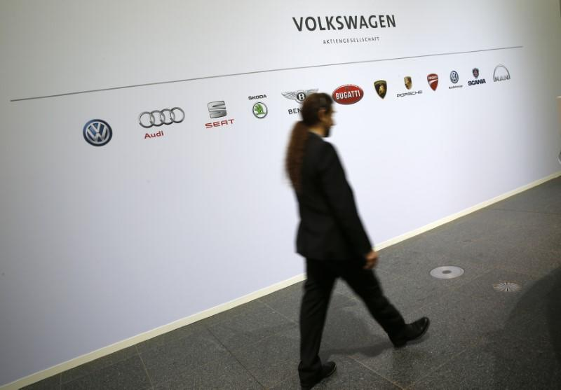 A man walks past the brands of the Volkswagen group during the annual news conference in Wolfsburg