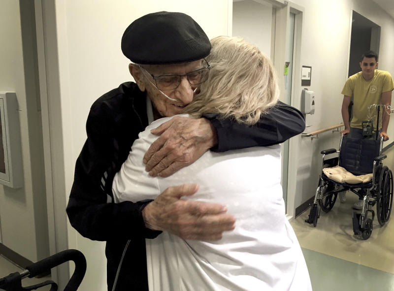 The Rev. John Sabbagh, left, and his son Ebby Sabbagh hugs nurse practitioner Kim O'Riley, Friday, Sept. 7, 2018 in Gilbert, Ariz. Thirty-five years after a Mesa man cared for his son when he was shot in their native Lebanon, the son is returning that devotion. Both the Rev. John Ibraham Sabbagh and his 54-year-old son, Ebby Sabbagh, are celebrating one year of going strong since the elder Sabbagh received a crucial stem-cell transplant. (AP Photo/Terry Tang)