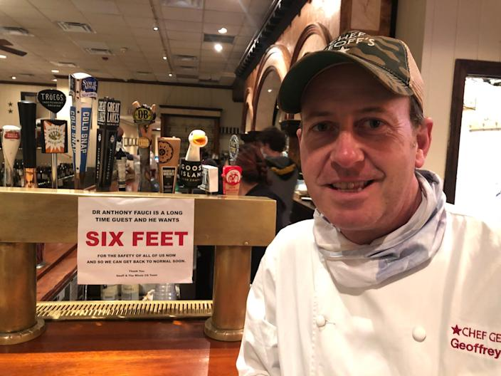 """Geoff Tracy, who runs Chef Geoff's in Washington, D.C., stands next to a sign inspired by a frequent diner, Anthony Fauci. Tracy says Fauci and his wife Christine are """"burger and beer"""" type patrons, and have stopped by on occasion for take-out during the pandemic."""