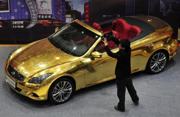 A man films a gold-plated Infiniti G37 at a jewelry store in Nanjing, Jiangsu province, March 31, 2011.