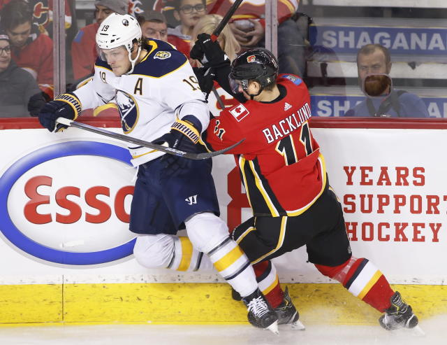 Buffalo Sabres' Jake McCabe, left, takes a hit from Calgary Flames Mikael Backlund, from Sweden, during the first period of an NHL hockey game Thursday, Dec. 5, 2019, in Calgary, Alberta. (Larry MacDougal/The Canadian Press via AP)