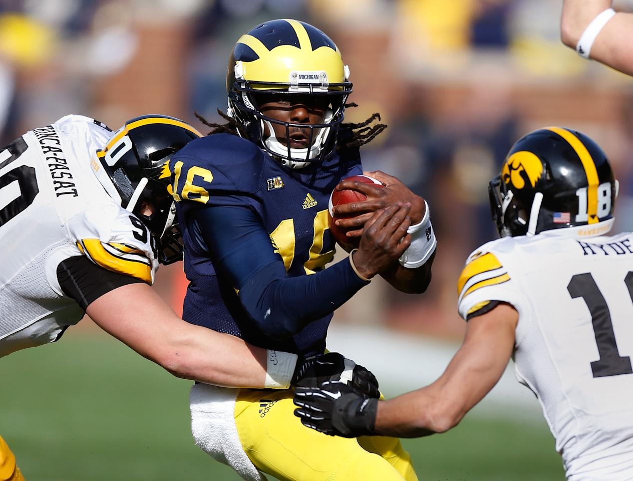 ANN ARBOR, MI - NOVEMBER 17:  Denard Robinson #16 of the Michigan Wolverines tries to split the tackles of Louis Trinca-Pasat #90 and Micah Hyde #18 of the Iowa Hawkeyes at Michigan Stadium on November 17, 2012 in Ann Arbor, Michigan. (Photo by Gregory Shamus/Getty Images)