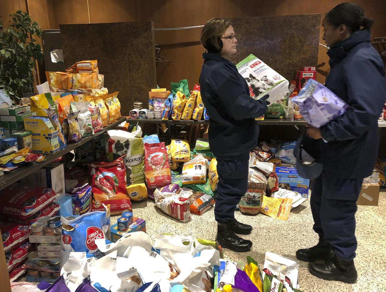 In this Thursday, Jan. 17, 2019 photo, members of the U.S. Coast Guard browse through bags of donated pet food at a pop-up pantry created by local Coast Guard-related advocacy groups to help the hundreds of civilian and non-civilian Coast Guard employees in New London, Conn., impacted by the partial federal shutdown. The outpouring from the community has been so great, the pantry has separate sections, including pet supplies, personal care and gluten-free food items. (AP Photo/Susan Haigh)