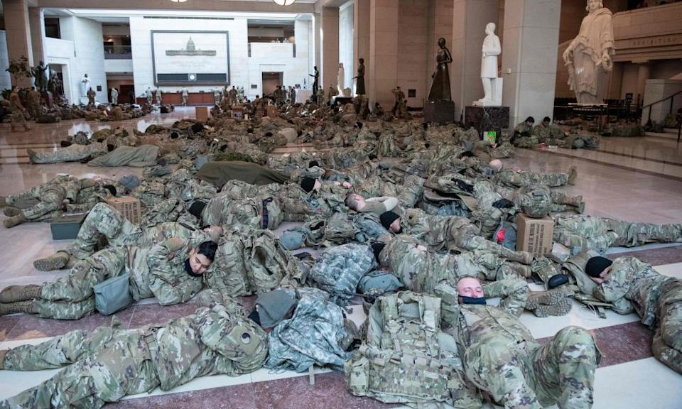 Members of the National Guard rest in the Capitol Visitors Center on Capitol Hill yesterday, ahead of an expected House vote to impeach President Donald Trump.