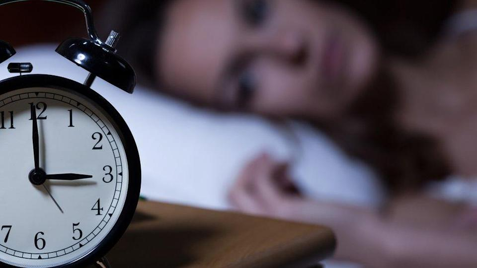 Close up of an alarm clock with a woman lying in bed in the background.