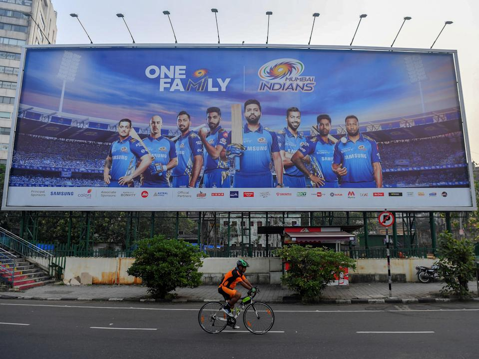 A cyclist rides past a hoarding of Mumbai Indians cricketers of the Indian Premier League (AFP via Getty Images)