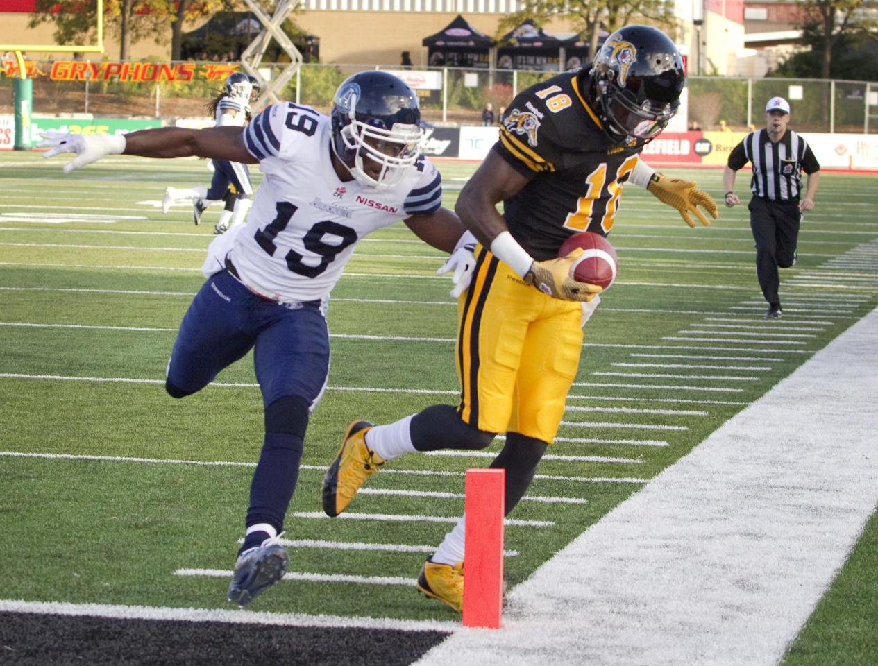 Hamilton Tiger-Cats' Dobson Collins (R) is pushed out of bounds just shy of the touchdown marker by Toronto Argonauts' Jalil Carter in the first half of their CFL football game in Guelph October 14, 2013. REUTERS/Fred Thornhill (CANADA - Tags: SPORT FOOTBALL)