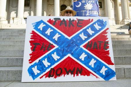 Jay Bender holds a sign asking for the removal of the Confederate battle flag that flies at the South Carolina State House in Columbia, SC June 20, 2015. REUTERS/Jason Miczek