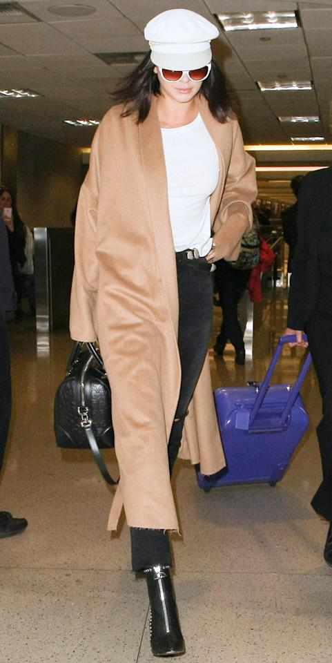 <p>Jenner was spotted at LAX in black jeans, a white top, camel-hued duster coat, and black booties. But the best part of her outfit? The white conductor hat and white-framed sunglasses that are giving us major Britney Spears circa 2002 vibes. </p>