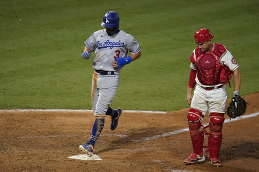 Los Angeles Dodgers' Chris Taylor, left, scores past Los Angeles Angels catcher Max Stassi on a sacrifice fly hit by Max Muncy during the 10th inning of a baseball game Saturday, Aug. 15, 2020, in Anaheim, Calif. The Dodgers won 6-5. (AP Photo/Marcio Jose Sanchez)