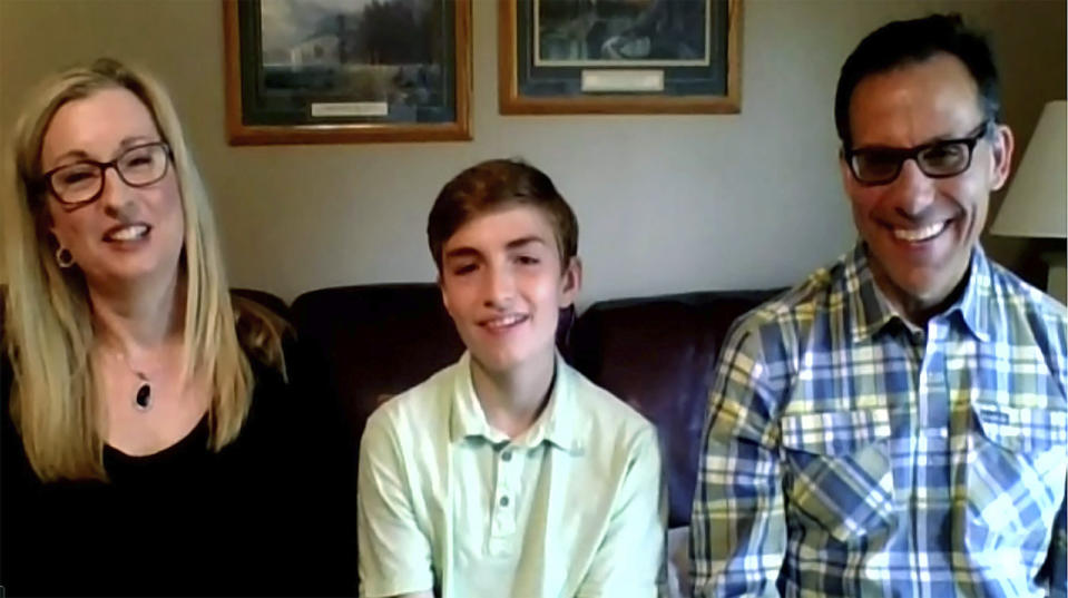 In this still image, taken from video by the Office of the Ohio Governor, eighth grader Joseph Costello, center, of Englewood, Ohio, the winner of the Ohio Vax-a-Million, full college scholarship vaccination incentive prize, is interviewed during a news conference, Thursday, May 27, 2021. He is joined by his parents Colleen and Rich Costello. (Office of Ohio Governor via AP)