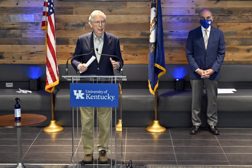 Senate Minority Leader Mitch McConnell, R-Ky., responds to a reporter's question during a news conference at a COVID-19 vaccination site in Lexington, Ky., Monday, April 5, 2021. At right is University of Kentucky President Eli Capilouto. (AP Photo/Timothy D. Easley)