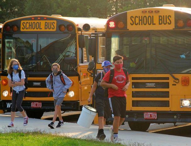 PHOTO: Williston Central School students get off the bus on their way to school in Williston, Vt., Sept. 8, 2020. Bus riders get their temperatures checked as they board the bus. (Elizabeth Murray/Burlington Free Press via USA Today Network)