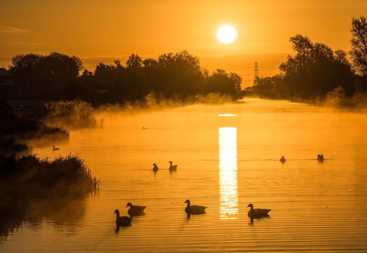 <p>The sun risis over the River Ouse near Ely, Cambridgeshire. (Rex Features) </p>