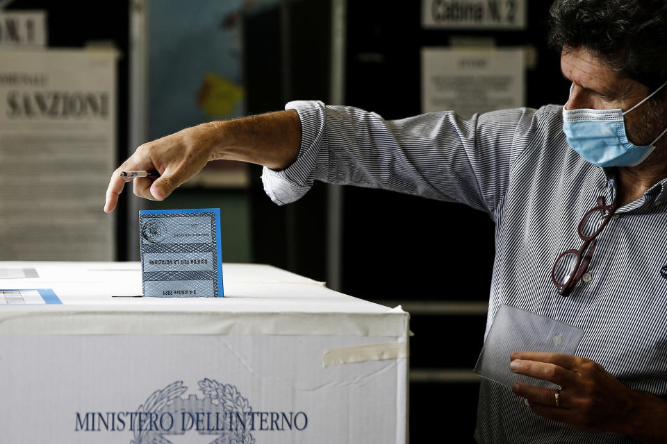 A man casts his ballots at a polling station, in Rome, Sunday, Oct. 3, 2021. Millions of people in Italy started voting Sunday for new mayors, including in Rome and Milan, in an election widely seen as a test of political alliances before nationwide balloting just over a year away. (Cecilia Fabiano/LaPresse via AP)
