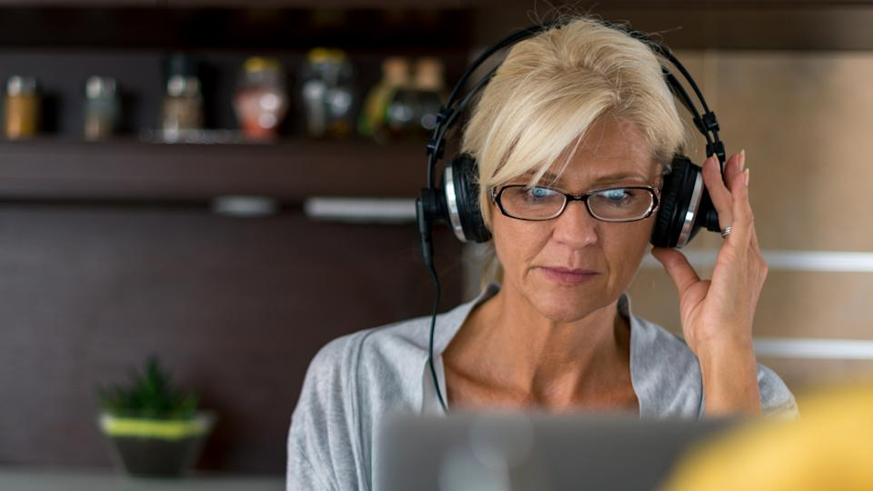 Senior woman listening to the music while surfing the net at home.