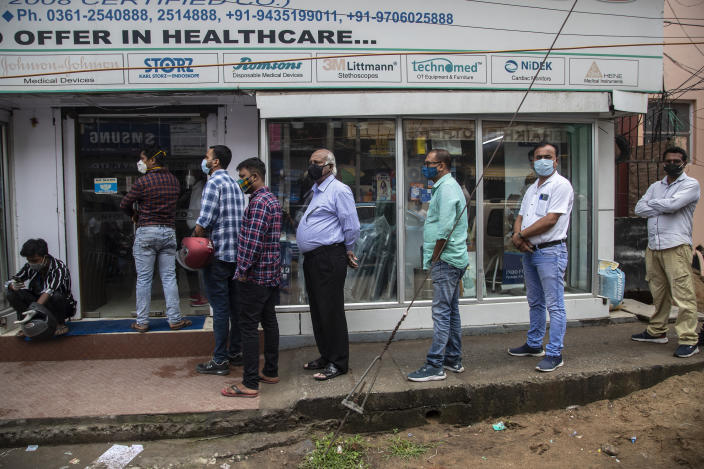 Indians wearing face masks as a precaution against the coronavirus line up outside a pharmacy to buy medicines in Gauhati, India, Thursday, May 6, 2021. Infections in India hit another grim daily record on Thursday as demand for medical oxygen jumped seven-fold and the government denied reports that it was slow in distributing life-saving supplies from abroad. (AP Photo/Anupam Nath)