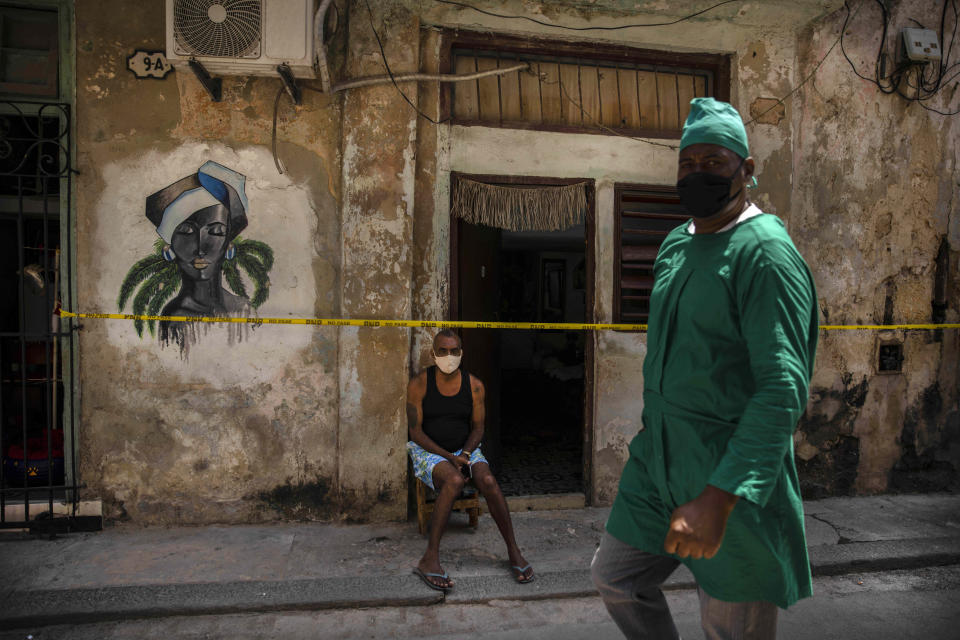 A health worker wearing a mask as a precaution against the spread of the new coronavirus walks in front of a man sitting at the entrance of his quarantined house in Havana, Cuba, Wednesday, April 7, 2021. (AP Photo/Ramon Espinosa)