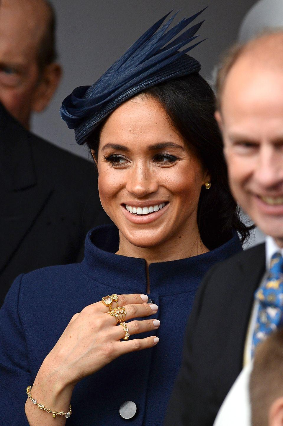 <p>Meghan layered up on gold rings for Princess Eugenie's 2018 wedding to Jack Brooksbank. </p>