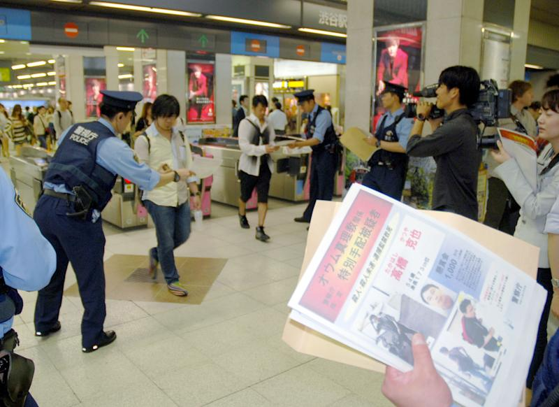 Police officers hand out wanted leaflets of Katsuya Takahashi, the last fugitive of the Aum Shinrikyo cult wanted as a murder suspect in the 1995 sarin nerve gas attack on Tokyo subways, to people at a railway station in Tokyo Friday, June 8, 2012. Thousands of police were mobilized Friday to hunt for Takahashi suspected in the deadly nerve gas attack, which killed 13 people and injured more than 6,000, 17 years ago. (AP Photo/Kyodo News) JAPAN OUT, MANDATORY CREDIT, NO LICENSING IN CHINA, HONG KONG, JAPAN, SOUTH KOREA AND
