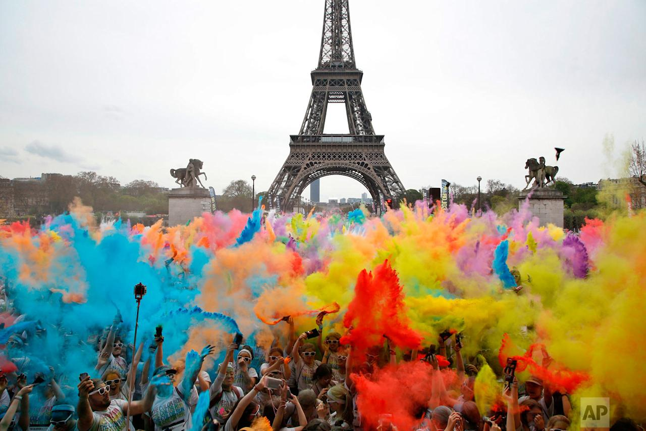 <p>People throw coloured powder as they celebrate at the end of the Colour Run 2018 race in front of the Eiffel Tower in Paris. The Colour Run is a 5 kilometer (3.1 mile) running event where participants are covered in bright coloured powder at each check station and is less about speed and more about enjoying a day with friends and family. (AP Photo/Thibault Camus) </p>