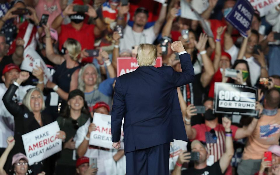 Donald Trump waves to the crowd as he leaves after speaking during a campaign event at the Orlando Sanford International Airport - Getty
