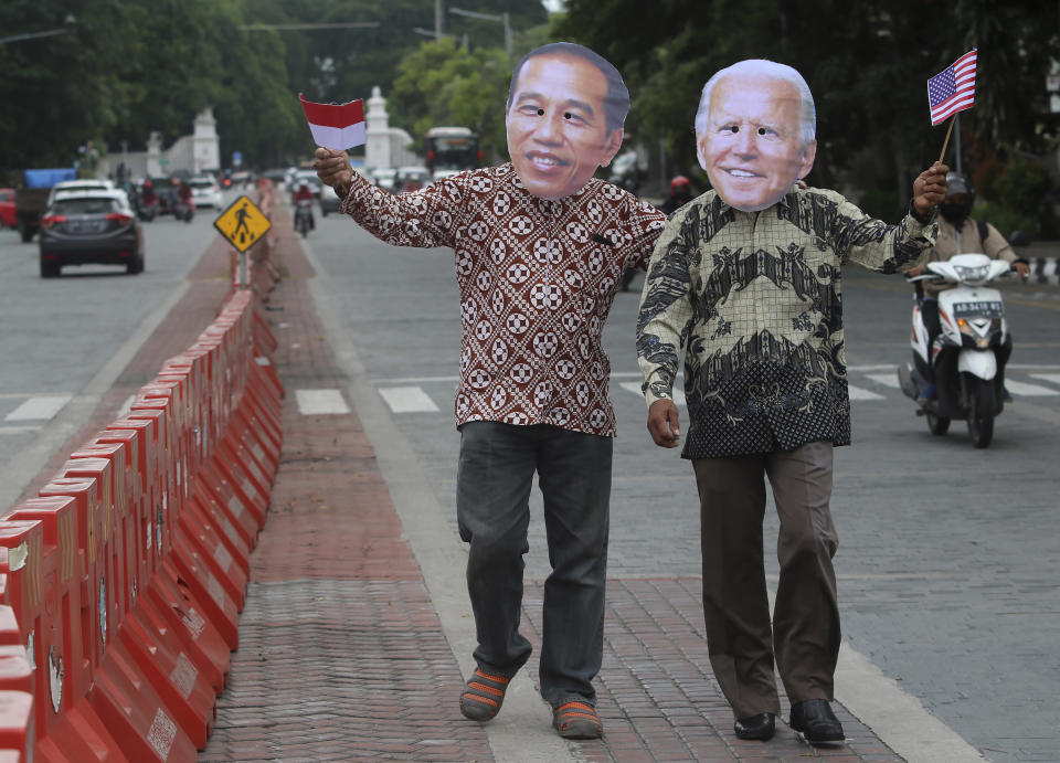 Local activists Mayor Haristanto, left, and Yenyen Wahyono wear masks of Indonesian President Joko Widodo and U.S. President-elect Joe Biden to congratulate him ahead of his inauguration ceremony, in Solo, Central Java, Indonesia, Wednesday, Jan. 20, 2021. (AP Photo/Sahistyo)