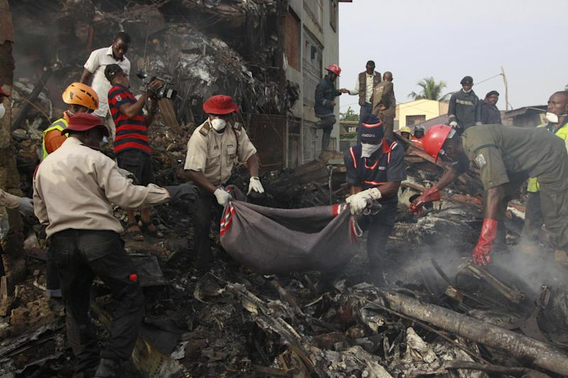 Rescue workers collect bodies from the scene of a plane crash in Lagos, Nigeria, Monday, June 4, 2012. A passenger plane carrying more than 150 people crashed in Nigeria's largest city on Sunday, government officials said. Firefighters pulled at least one body from a building that was damaged by the crash and searched for survivors as several charred corpses could be seen in the rubble.(AP Photo/Sunday Alamba)