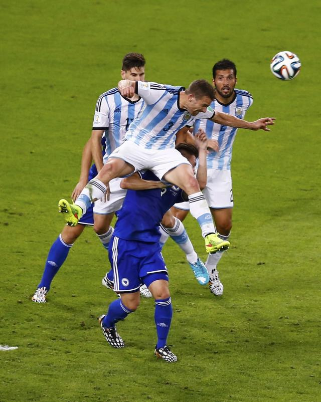 Argentina's Hugo Campagnaro jumps to clear the ball during their 2014 World Cup Group F soccer match against Bosnia at the Maracana stadium in Rio de Janeiro June 15, 2014. REUTERS/Ricardo Moraes (BRAZIL - Tags: SOCCER SPORT WORLD CUP)