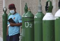A man waits by his empty oxygen tank in a line of other customers outside a shop that refills them in the Villa El Salvador shantytown of Lima, Peru, Thursday, Jan. 21, 2021, amid the COVID-19 pandemic. (AP Photo/Martin Mejia)