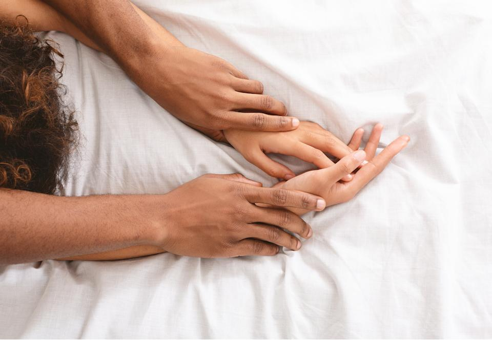 Black man and woman enjoying sexual foreplay in bed, free space