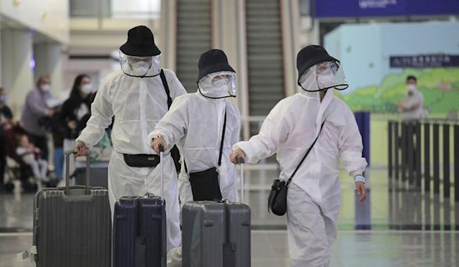 Passengers wear protective suits and face masks as they arrive at Hong Kong airport. Photo: AP