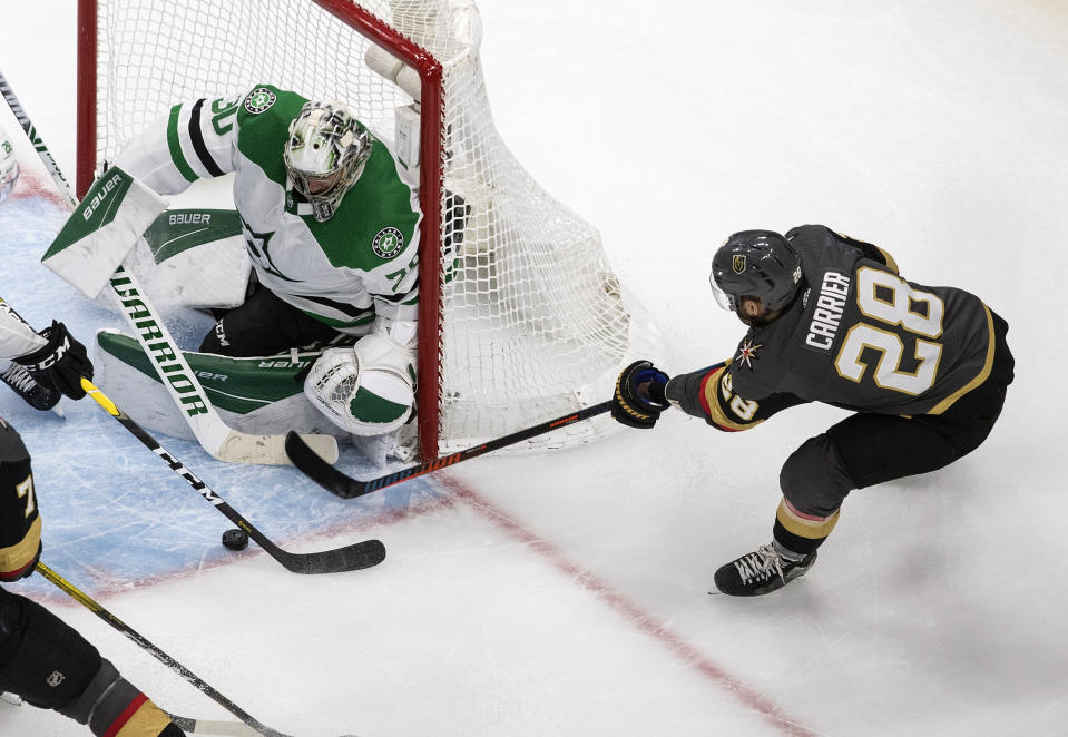 Dallas Stars goalie Ben Bishop (30) makes the save on Vegas Golden Knights' William Carrier (28) during the third period of an NHL hockey playoff game Monday, Aug. 3, 2020 in Edmonton, Alberta. (Jason Franson/The Canadian Press via AP)