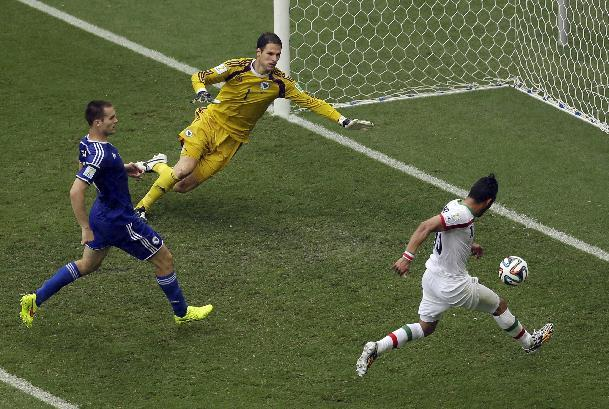 Iran forward Reza Ghoochannejhad, right, scores past Bosnia goalie Asmir Begovic as Bosnia midfielder Senad Lulic looks on during the second half of a group F World Cup soccer match at the Arena Fonte Nova in Salvador, Brazil, Wednesday, June 25, 2014