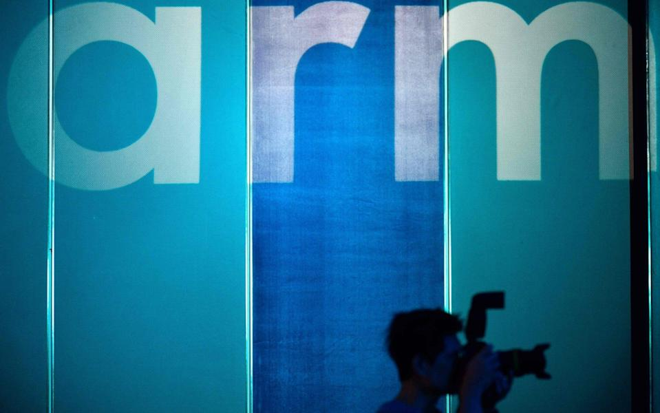 A photographer taking pictures in front of the logo for British chip designer Arm - SAM YEH/AFP