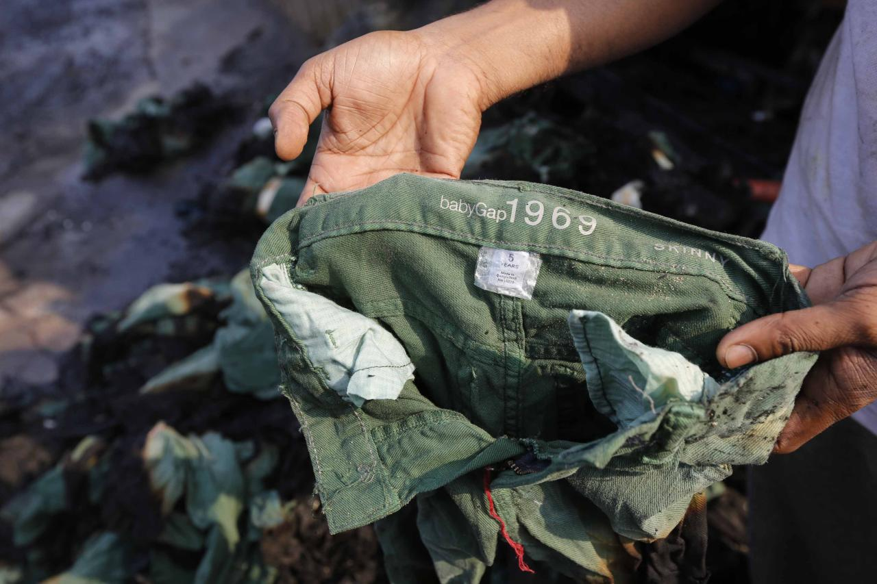 An employee shows the brand of a burnt clothing item in front of a Standard Group garment factory which was on fire in Gazipur November 29, 2013. A huge fire on Friday destroyed the Bangladesh garment factory supplying key Western brands, authorities said, in a blaze touched off by workers angered over rumours of a colleague's death in police firing. There were no initial reports of casualties in the fire. Police broke up a clash with the workers with tear gas, but hundreds of workers gathered later, vandalized the factory, set two buildings on fire, and blockaded the road, said Mushfiqur Rahman, a manager at Standard Garments, a firm in the building. REUTERS/Andrew Biraj (BANGLADESH - Tags: DISASTER BUSINESS)