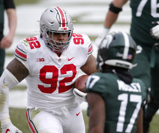 Ohio State's Haskell Garrett, left, scores against Michigan State's Tre Mosley after deflecting and catching a Michigan State pass in the end zone during the first half of an NCAA college football game, Saturday, Dec. 5, 2020, in East Lansing, Mich. (AP Photo/Al Goldis)