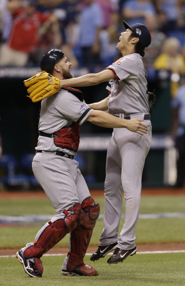Boston Red Sox pitcher Koji Uehara, right, jumps on catcher Jarrod Saltalamacchia, after the team defeated the Tampa Bay Rays in Game 4 of an American League baseball division series, Wednesday, Oct. 9, 2013, in St. Petersburg, Fla. The Boston Red Sox's defeated the Tampa Bay Rays 3-1 to move on to the American League Championship Series. (AP Photo/Chris O'Meara)