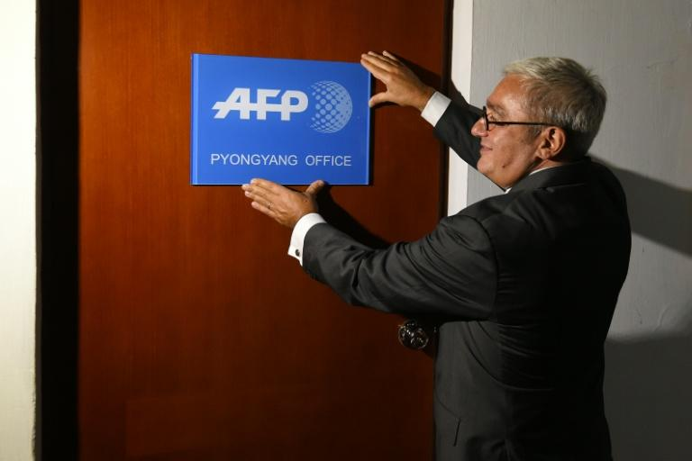 Chief Executive and Chairman of Agence France-Presse Emmanuel Hoog hangs a company sign on the door of the news agency's bureau in Pyongyang, North Korea on September 6, 2016