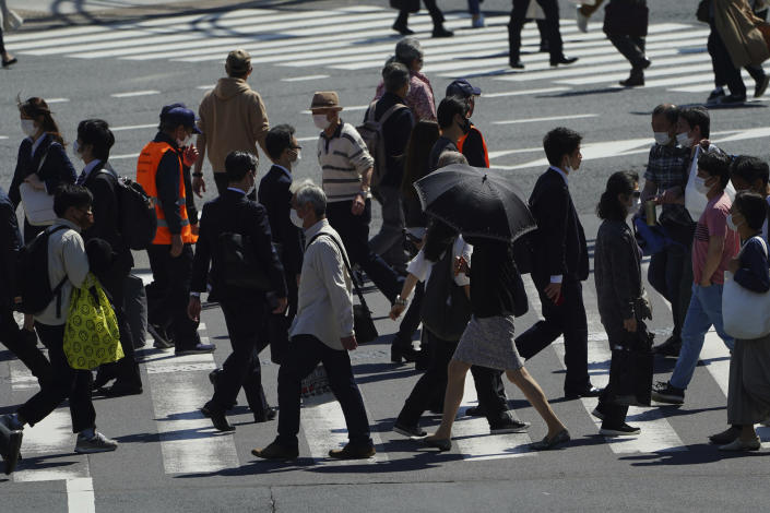 People wearing protective masks to help curb the spread of the coronavirus walk along a pedestrian crossing Wednesday, April 21, 2021, in Tokyo. The Japanese capital confirmed more than 840 new coronavirus cases on Wednesday. (AP Photo/Eugene Hoshiko)
