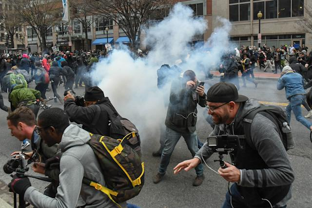Protesters and journalists scramble as stun grenades are deployed by police during the demonstrations on Jan. 20.