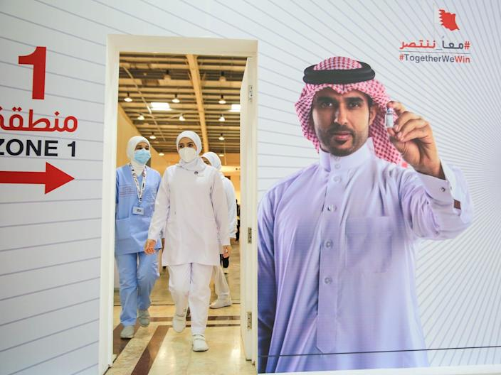Nurses wearing masks walk through a doorway. On the wall is a poster or a man holding a vial of COVID-19 vaccine.