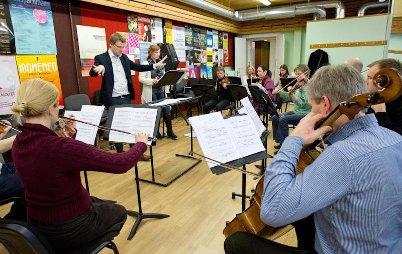 """Conductor Risto Joost, rear left, and soprano Iris Oja rehearse the operetta """"Nostra Culpa"""" in Tallinn, Estonia, Thursday, April 4, 2013. Inspired by a lively social media exchange between Estonian President Toomas Hendrik Ilves and Nobel Prize-winning economist Paul Krugman, the two expats, composer Eugene Birman and Scott Diel, who wrote the lyrics, have composed an operetta that soars across the merits and pitfalls of austerity _ an ever more prominent reality in Europe's struggling economy. (AP Photo/Liis Treimann)"""