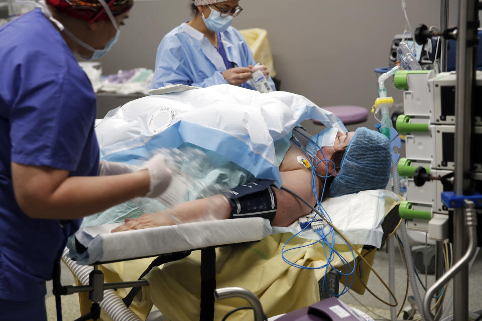 Medical staff and surgeon Lara Ribeiro Parenti, right, start the preparations for the surgery of Caroline Erganian at Bichat Hospital, AP-HP, in Paris, Wednesday, Dec. 2, 2020. Erganian, 58, hopes to shed more than a third of her weight as a result of having a large part of her stomach cut out and be free of knee and back pain — and of her cane. She prayed in the final weeks that her phone wouldn't ring with news of another delay. (AP Photo/Francois Mori)