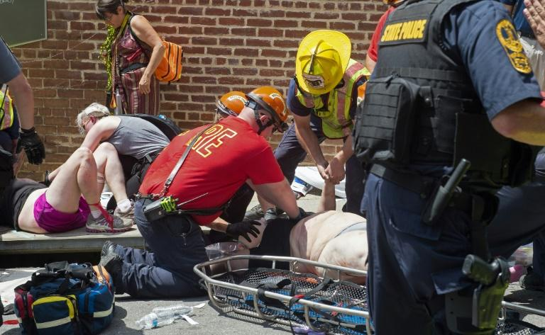 Injured people receive first-aid after a car plowed into a crowd of protesters in Charlottesville, Virginia, on August 12, 2017