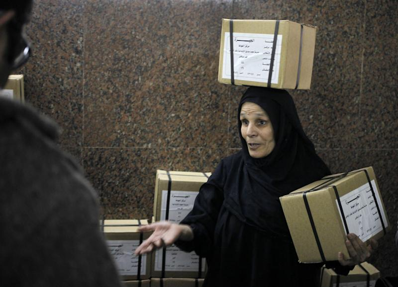 "An Egyptian worker carries boxes of ballots at the Giza courthouse, in Cairo, Egypt, Monday, Jan. 13, 2014. The January 14-15 vote on the draft constitution will be the first real test of the post-Morsi regime. A comfortable ""yes"" vote and a respectable turnout would be seen as bestowing legitimacy, while undermining the Islamists' argument that Morsi remains the nation's elected president. (AP Photo/Amr Nabil)"