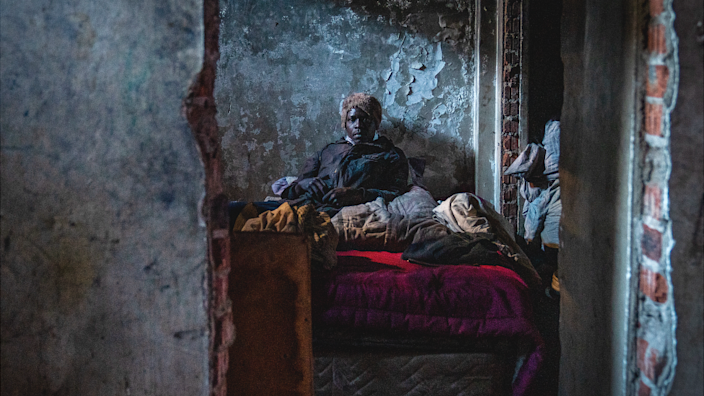 An unidentified man sitting on his bed in one of the makeshift rooms in the derelict San Jose building in Johannesburg, South Africa