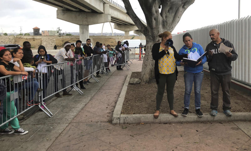 """Volunteers in Tijuana, Mexico, call names from from a waiting list of people to claim asylum at a border crossing in San Diego Thursday, Sept. 26, 2019. The Trump administration played """"bait and switch"""" by instructing migrants to wait in Mexico for an opportunity to apply for asylum before imposing sharp restrictions on eligibility, attorneys said in a court filing Thursday. (AP Photo/Elliot Spagat)"""