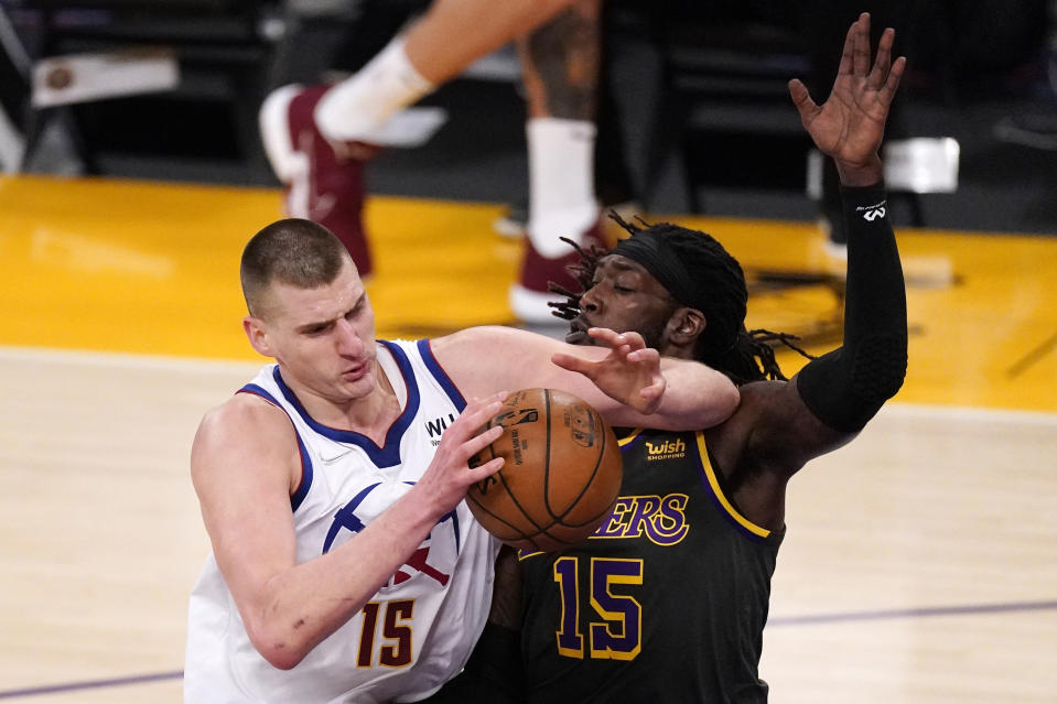 Denver Nuggets center Nikola Jokic, left, elbows past Los Angeles Lakers center Montrezl Harrell during the first half of an NBA basketball game Monday, May 3, 2021, in Los Angeles. (AP Photo/Mark J. Terrill)